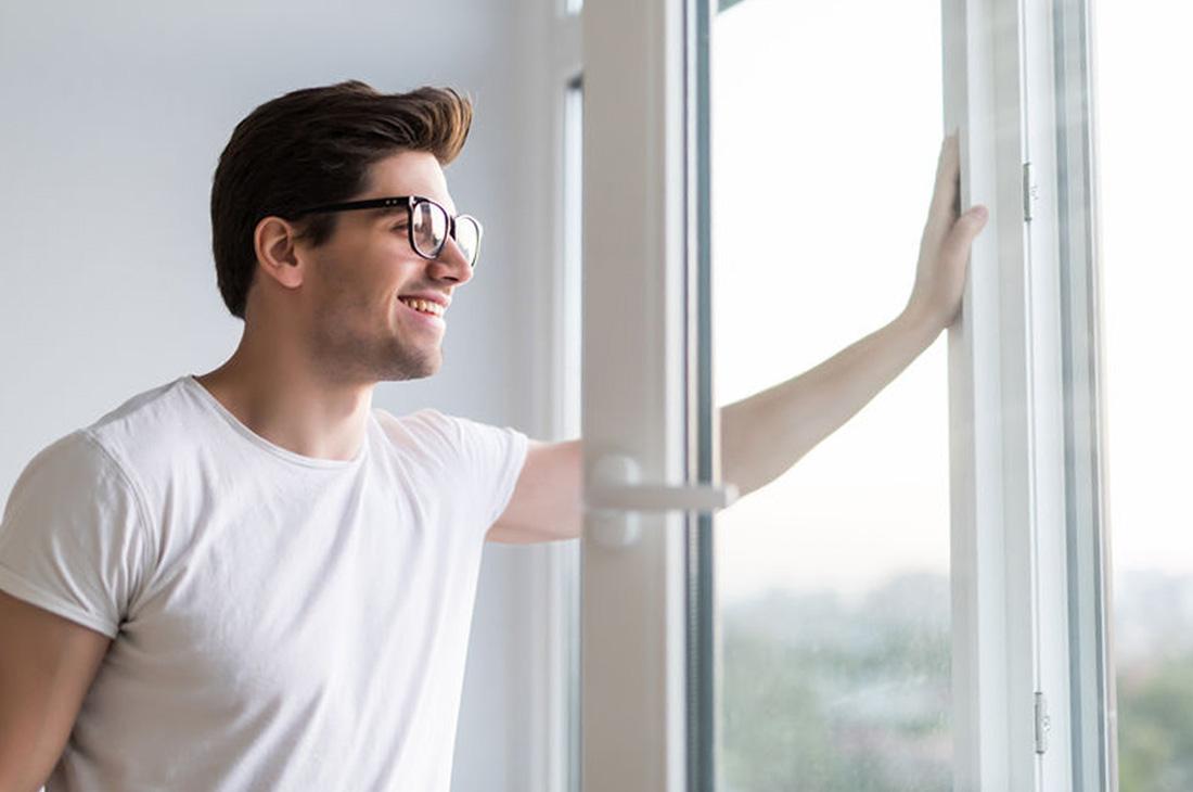 Man opening window in an office